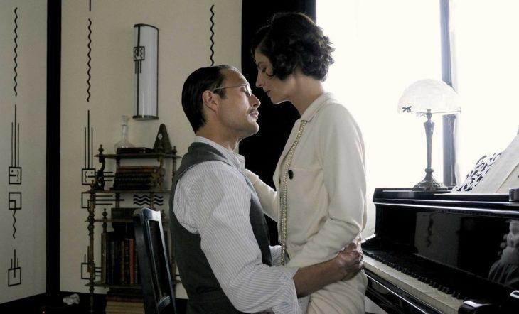 mujer sentada en piano con hombre de lentes