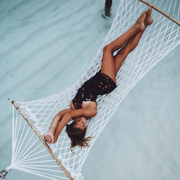 mujer acostada en hamaca sobre la playa
