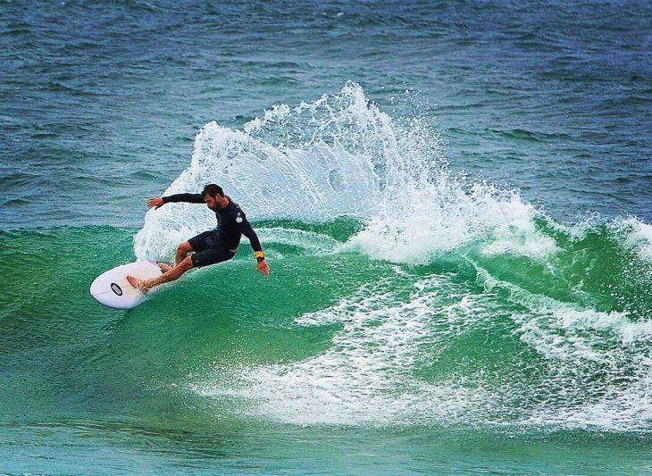 hombre en tabla de surf y olas en el mar