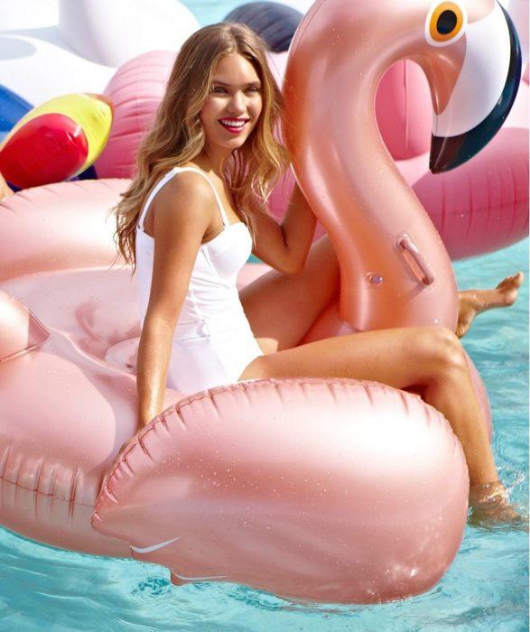 mujer rubia con traje de baño sentada arriba de un flamingo