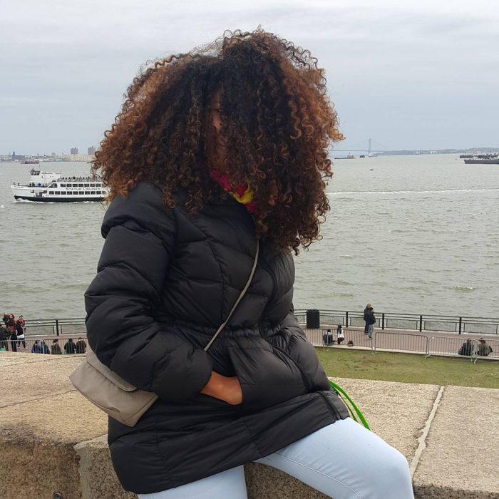 chica de cabello largo rizado con chamarra junto al lago