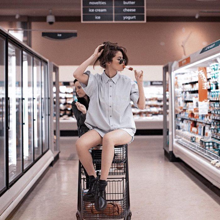 mujer con camisa y cabello agarrado con lentes sobre carro de supermercado