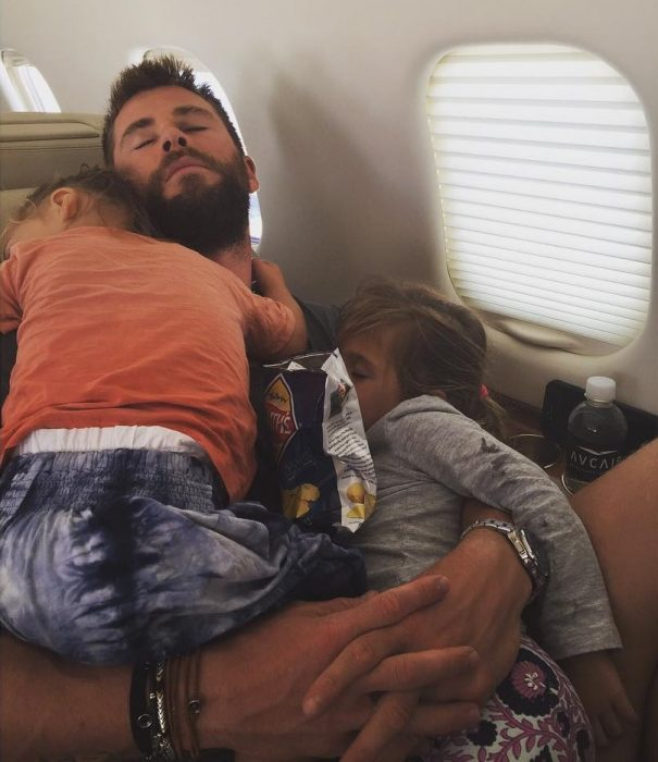 hombre en asiento de avion con dos niños dormidos