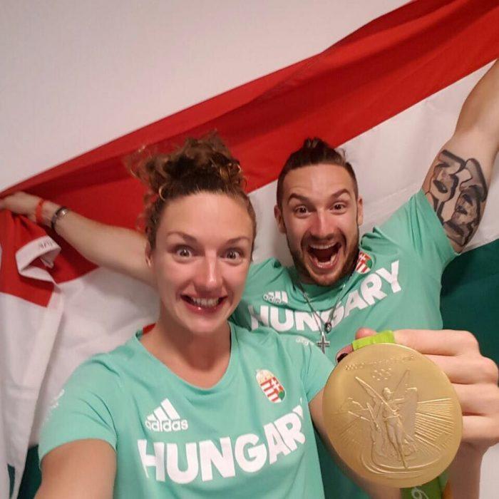 hombre y mujer con camisa verde, medalla de oro y bandera
