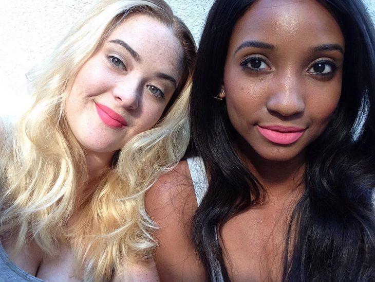 Dos mujeres de piel blanca y morena con labial rosa