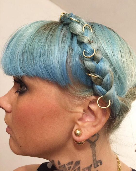 mujer rubia con cabello azul, fleco y anillos