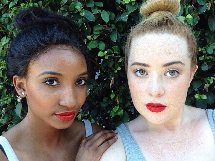 Dos mujeres de piel blanca y morena con labial rojo