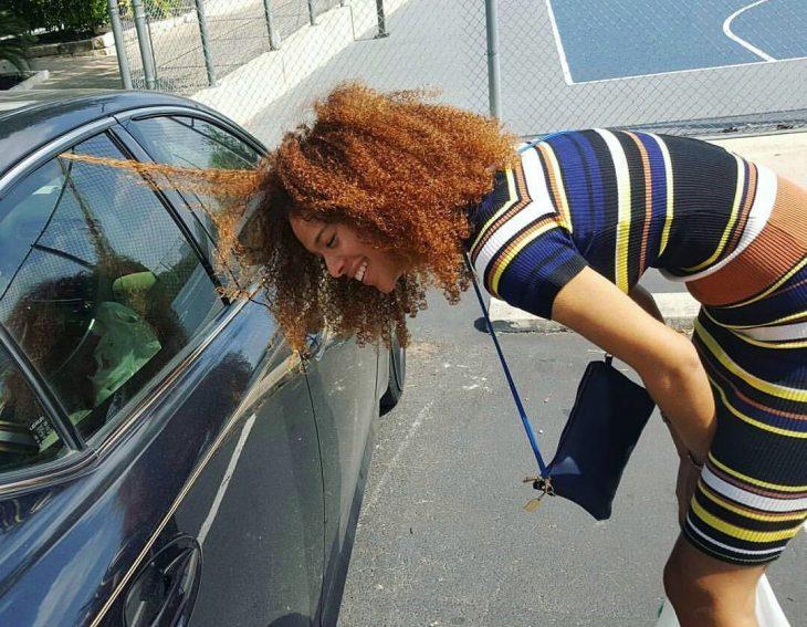 chica de cabello largo rizado con mechon atorado en vidrio