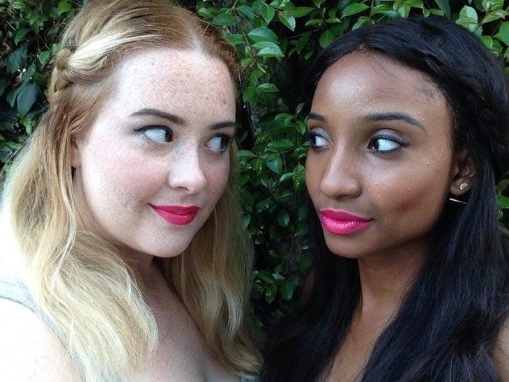 Dos mujeres de piel blanca y morena con labial rosa fuerte
