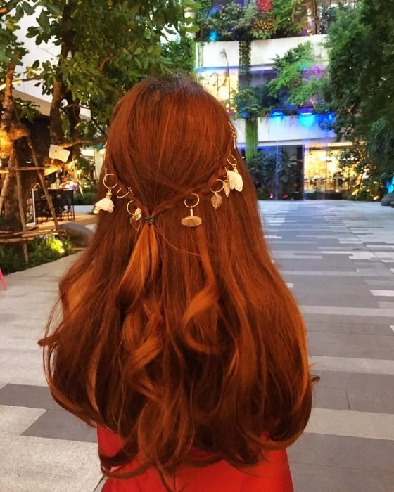 mujer cabello largo y anillos con plumas
