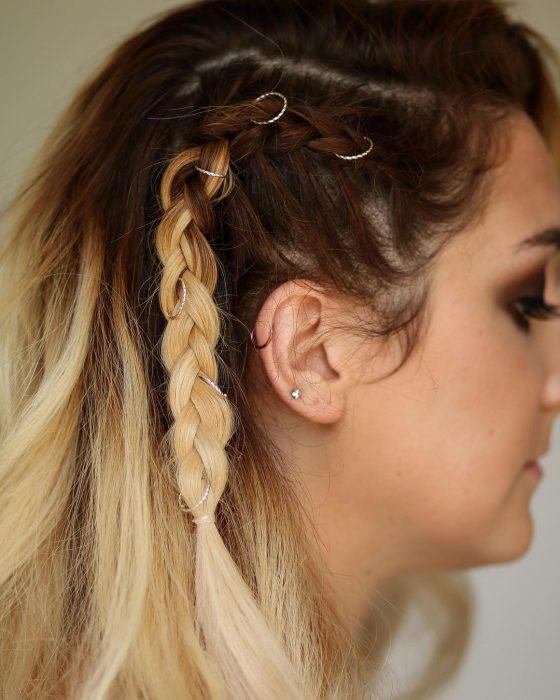 mujer con cabello castaño y rubio con anillos
