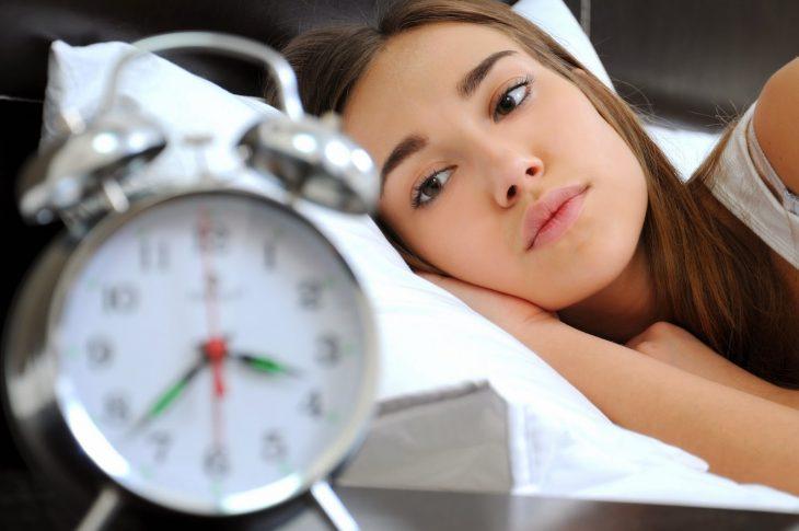 mujer acostada mirando el del despertador