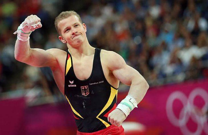 hombre musculoso atleta rubio levanta el puño