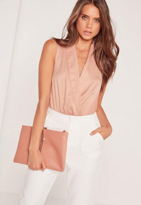 Chica usando un bodysuit en color rosa con un pantalón blanco