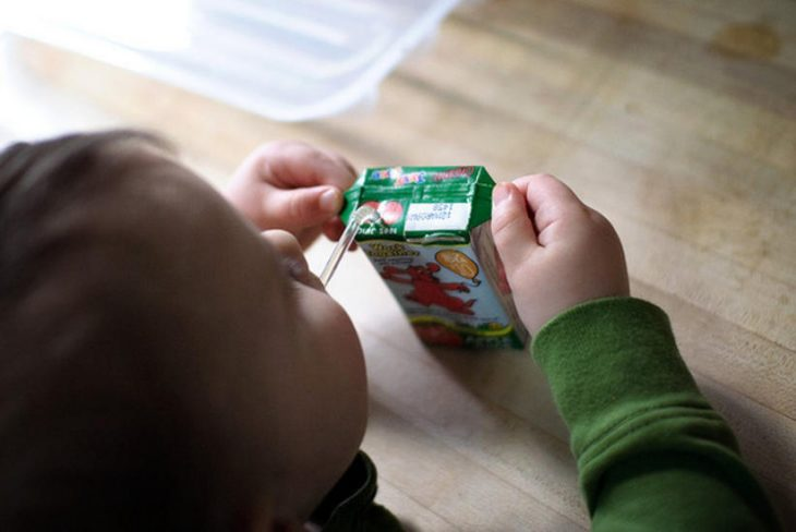 niño tomando jugo de cajita