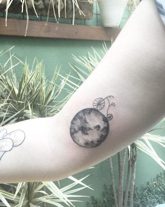 tatuaje mundo y bicicleta