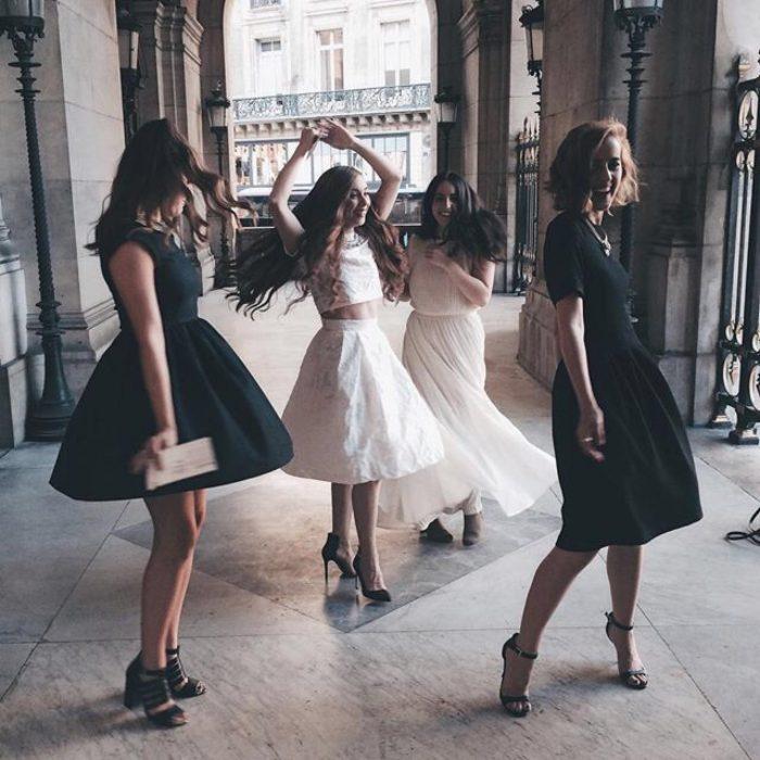 mujer con vestido blanco bailando con otras mujeres