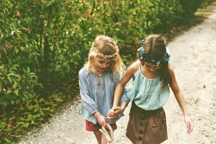 niñas con flores en la cabeza tomadas de la mano