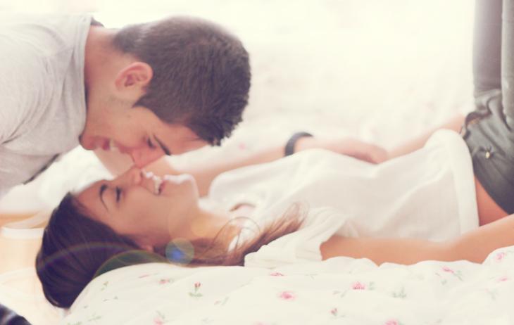 Chica recostada en una cama mientras su pareja le da un beso en la nariz