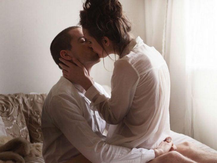 Pareja de novios besándose mientras están sentados en la cama