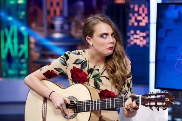 chica tocando guitarra haciendo caras