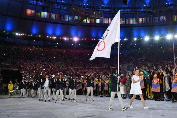 grupo de personas caminando en medio de estadio con bandera de juegos olímpicos