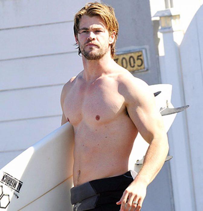 hombre rubio sin playera con tabla de surf