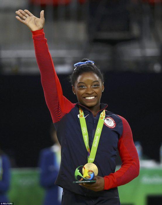 mujer morena con medalla levanta la mano