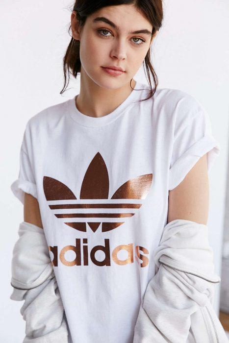 Mujer blanca con playera blanca y logo adidas rose gold