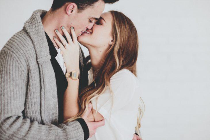 Chica acariciando la mejilla de su pareja mientras lo besa