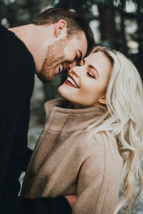 Pareja de novios besándose y sonriendo