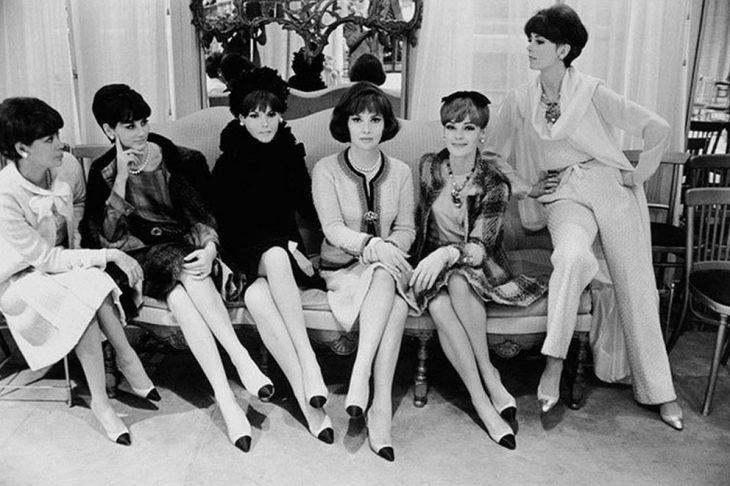 mujeres sentadas en sillón con zapatos blancos y punta negra