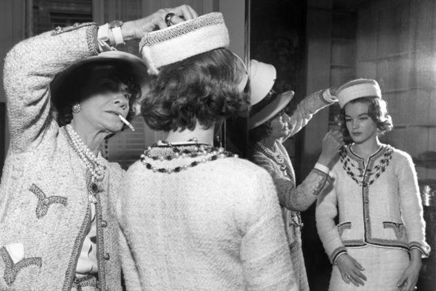 mujer con sombrero arreglando sombrero de mujer frente al espejo