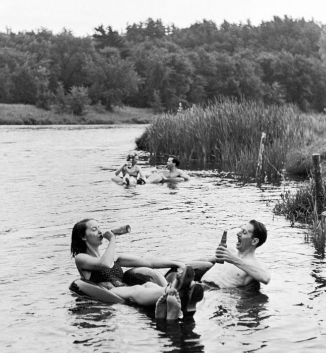 parejas bebiendo y nadando en un río.