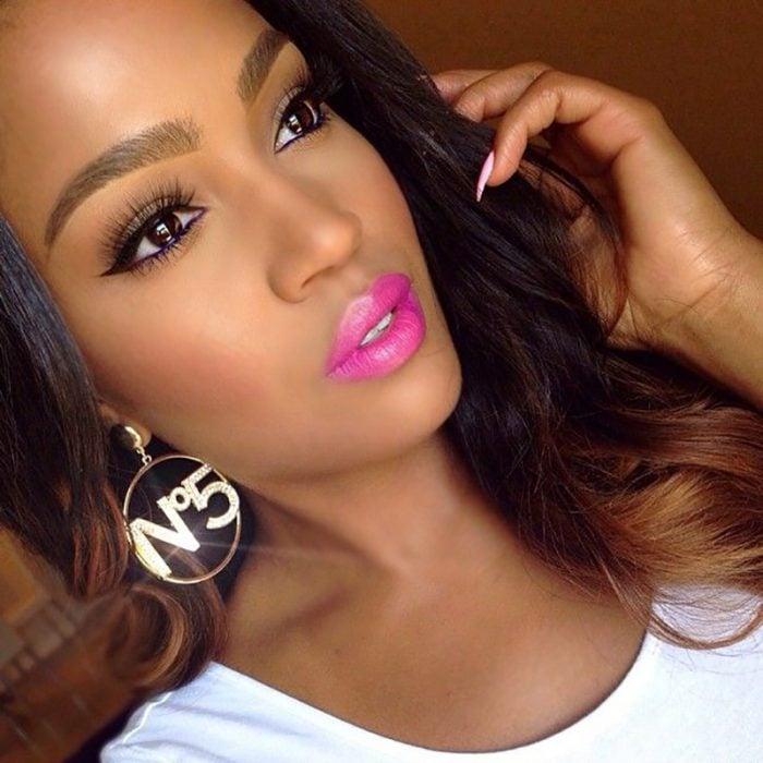 mujer morena con labios rosas y aretes de oro