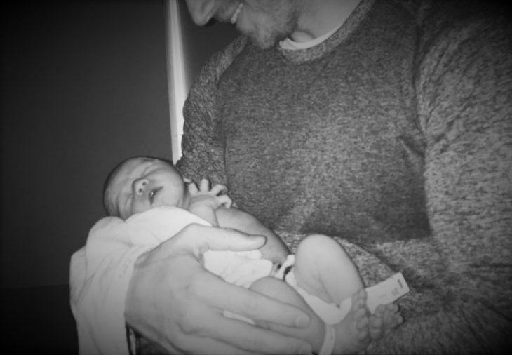 hombre con camisa gris cargando a bebe