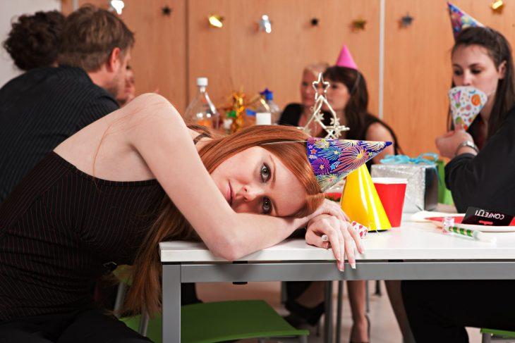 Chica en una fiesta de cumpleaños aburrida mientras está recostada sobre una mesa
