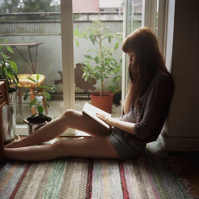 Chica sentada en el suelo mientras está leyendo un libro