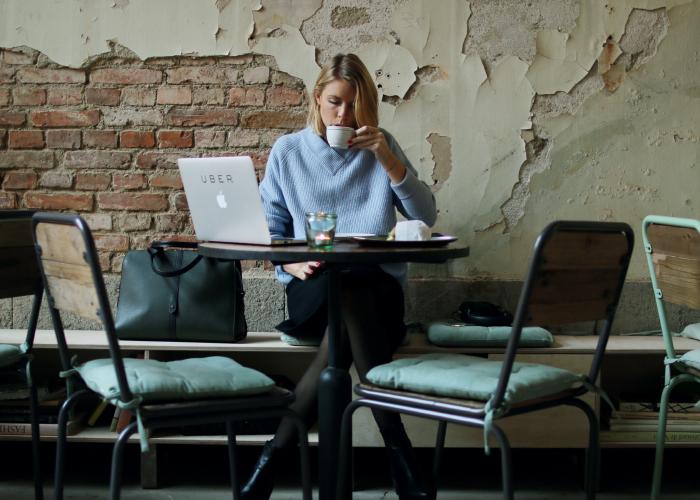 Chica sentada en un café revisando su computadora