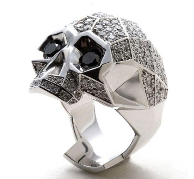 Anillo en forma de calavera de color plata con piedras en color negro