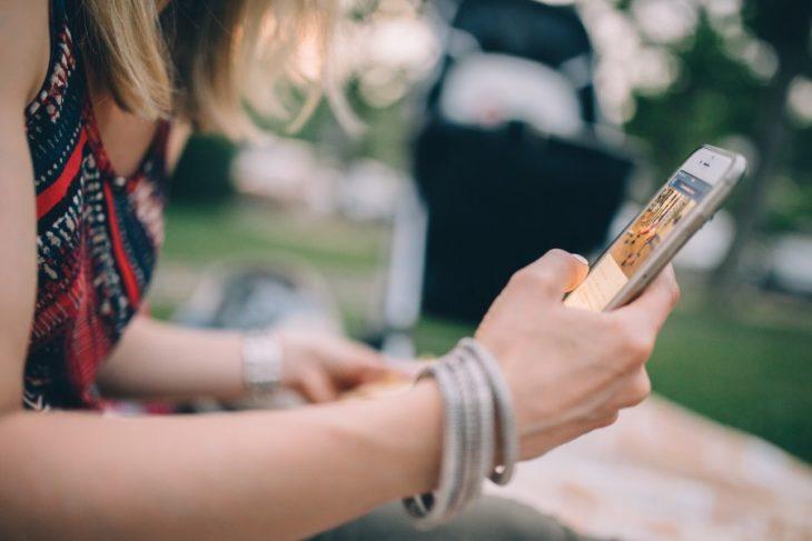mujer con celular en mano