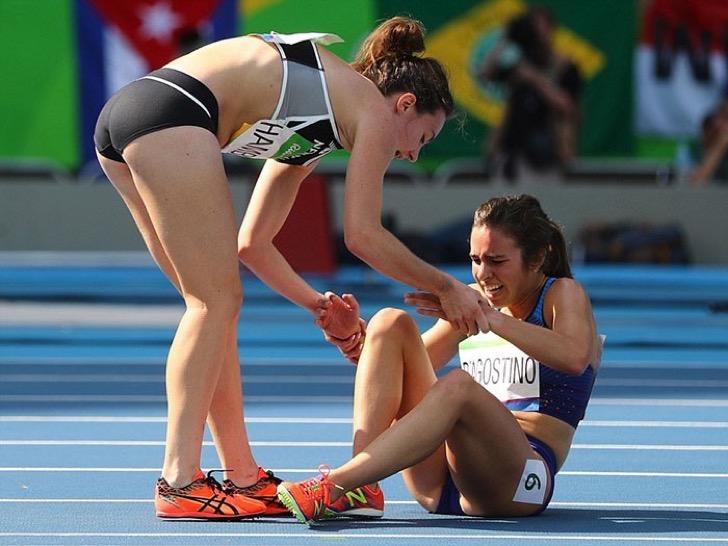 Chica corredora ayudando a otra a levantarse