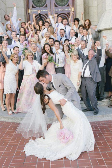 Pareja el día de su boda besándose mientras sus familias festejan atrás de ellos