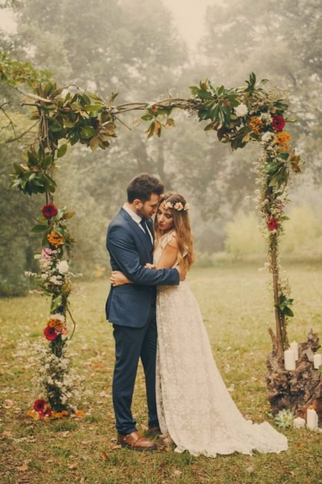 Pareja de novios con una boda boho parados bajo un marco de madera con flores