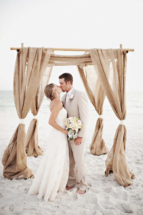 Pareja besándose el día de su boda en la playa