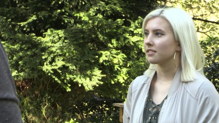 mujer blanca de cabello rubio con aretes