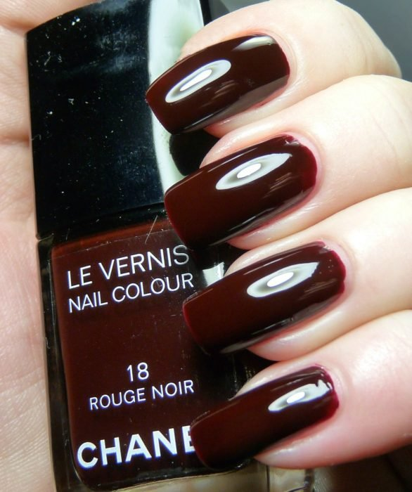 mano con esmalte de color vino chanel