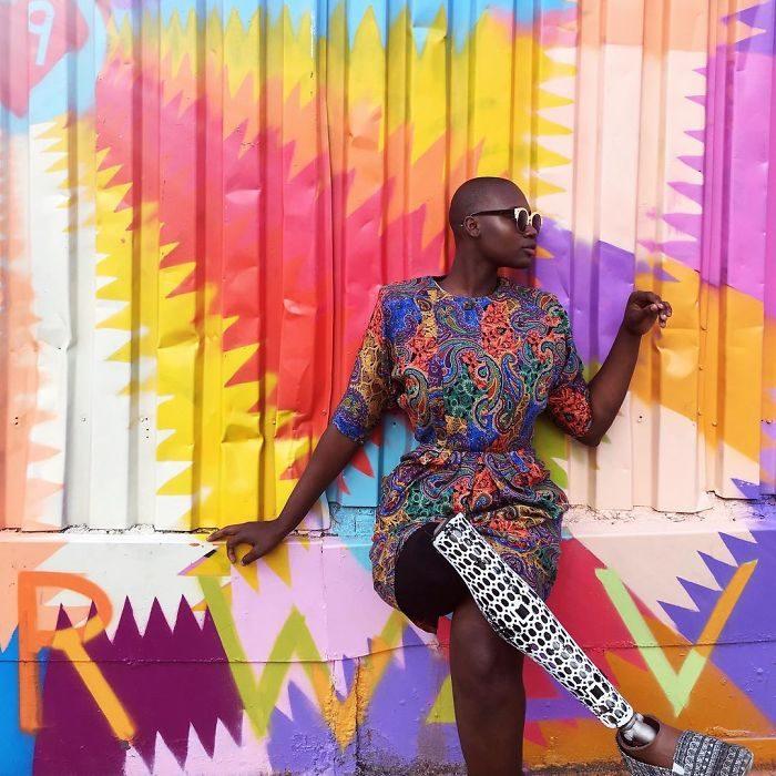 Blogger de belleza con una pierna amputada sentada frente a una pared posando para una fotografía