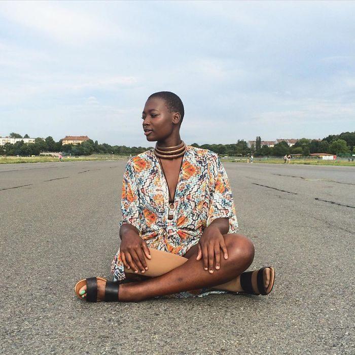 blogger de belleza con una pierna amputada sentada en medio de la carretera posando para una fotografía