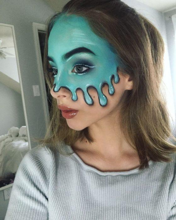 Chica crea maquillaje de fantasía de una gran mancha azul corriendo por su rostro